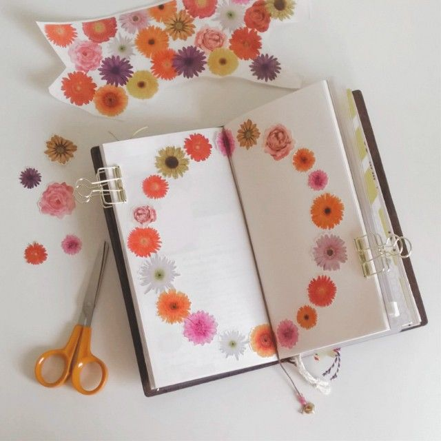 Cutting and pasting flowers from paper that was wrapped around some flowers.