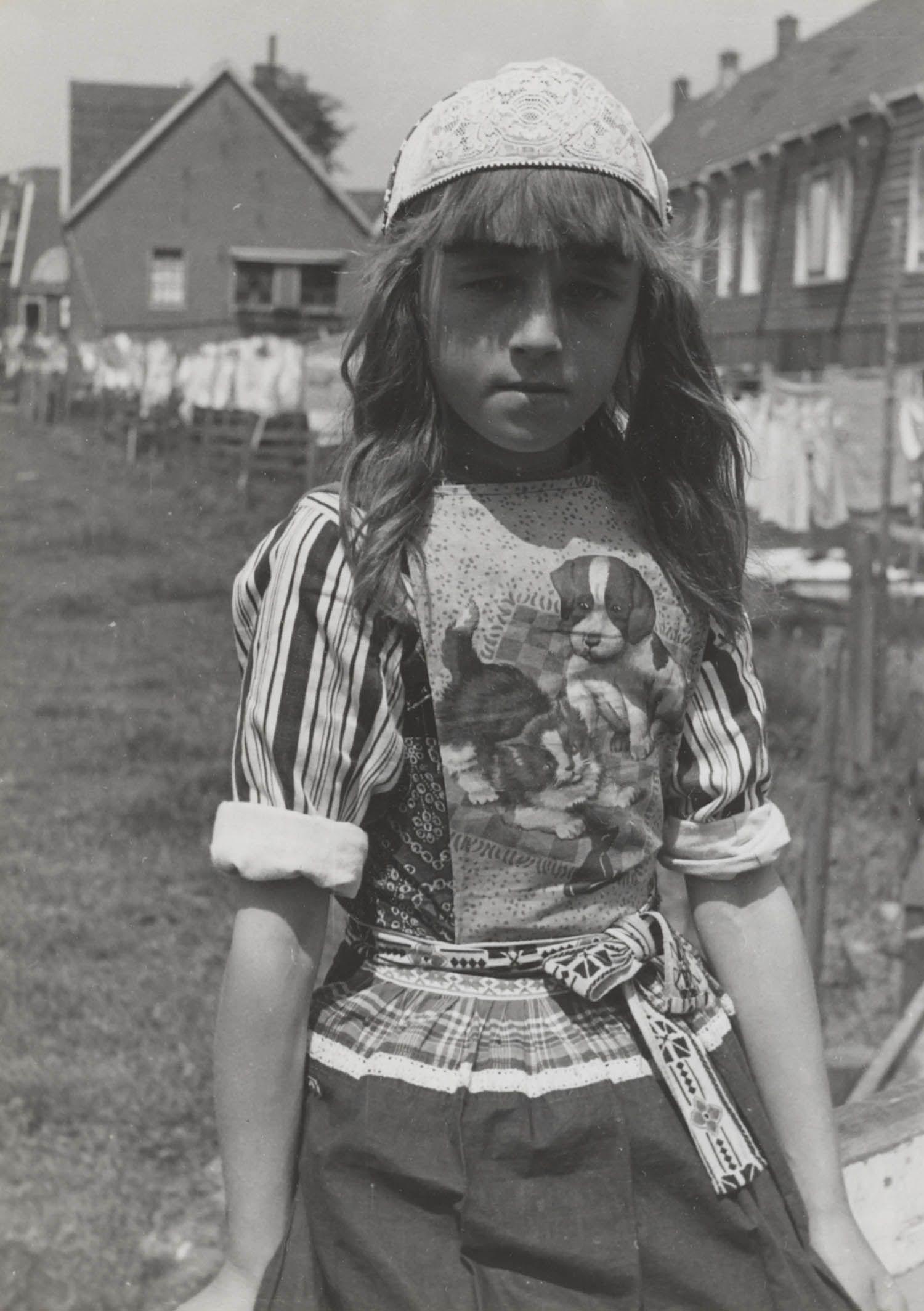 Jong meisje in Marker streekdracht. Ze draagt een 'bauw' (borstlap) met daarop een poes en een hond. 1943 #NoordHolland #Marken