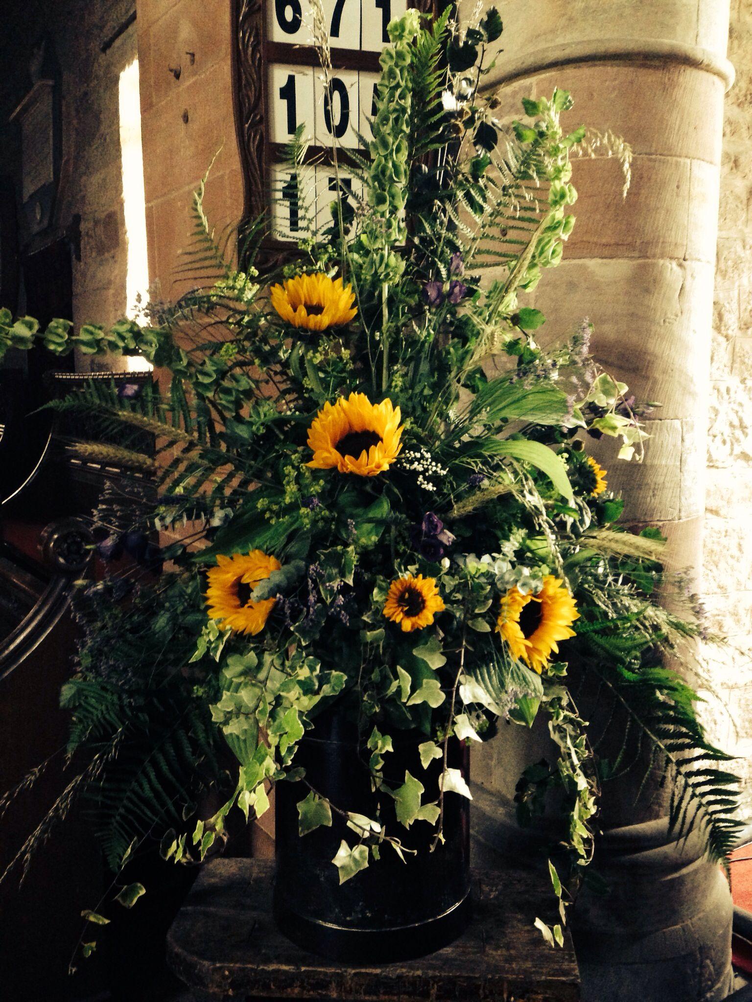 Sunflower and mollucella pedestal arrangement at dacre