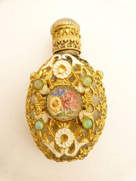 This lovely miniature perfume bottle is signed on the cap CZECHO SLOVAKIA. It has gold tone filigree wrap with white enamel and tiny green glass cabochons. The center is set with a flowered goofus glass cabochon as is the top of the cap - very unique for these pieces. The bottle measures