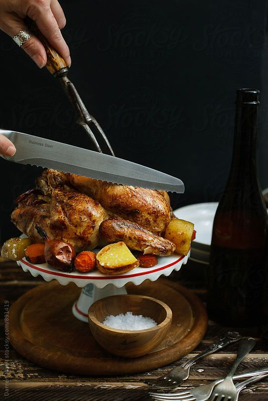 Woman's hands using a carving fork and knife to carve a whole roast chicken.