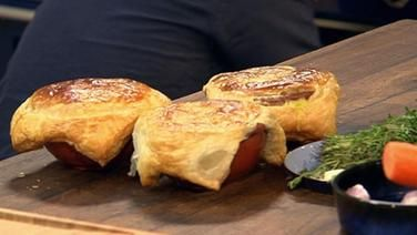 Drei mit Blätterteig überbackene Ofenformen aus rotem Ton.