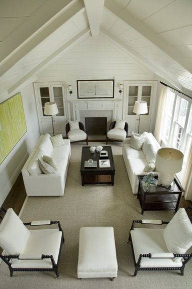 classic white + vaulted ceiling + yellow-green art....love this seating arrangement for a smaller space