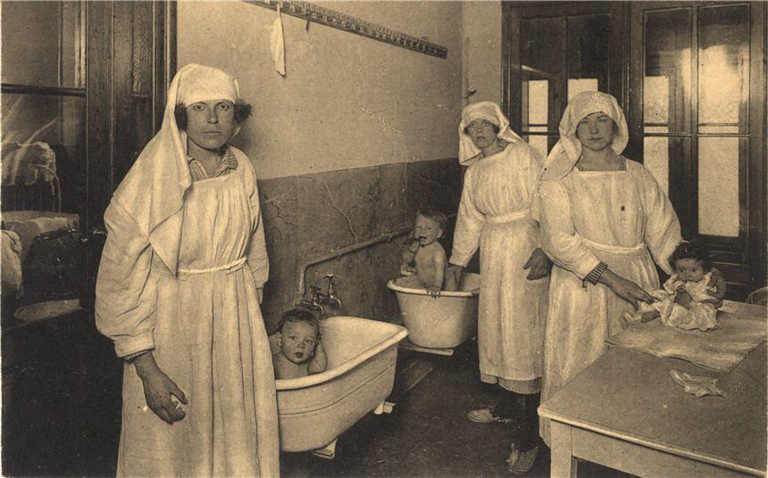 Three White female nurses tend to three White babies, two of which ...