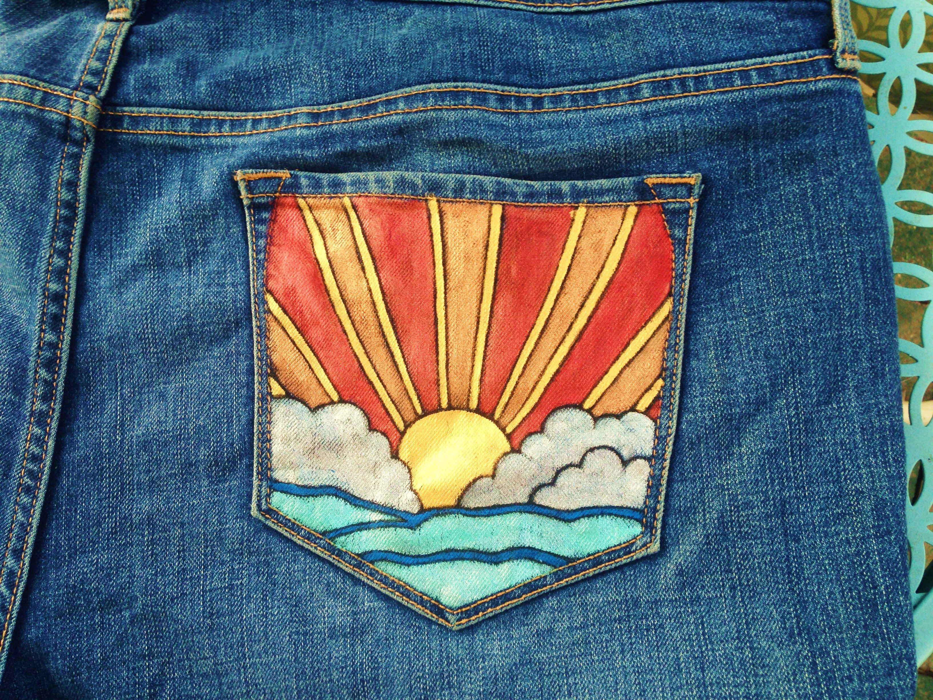 Sunset on the water painted on the back of a pair of jeans