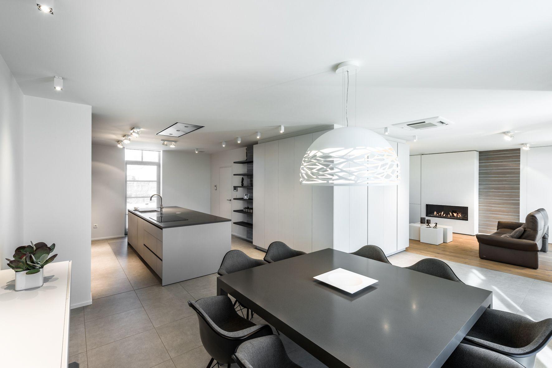 Woonkamer met haard en keukeneiland in een modern interieur door Ken ...