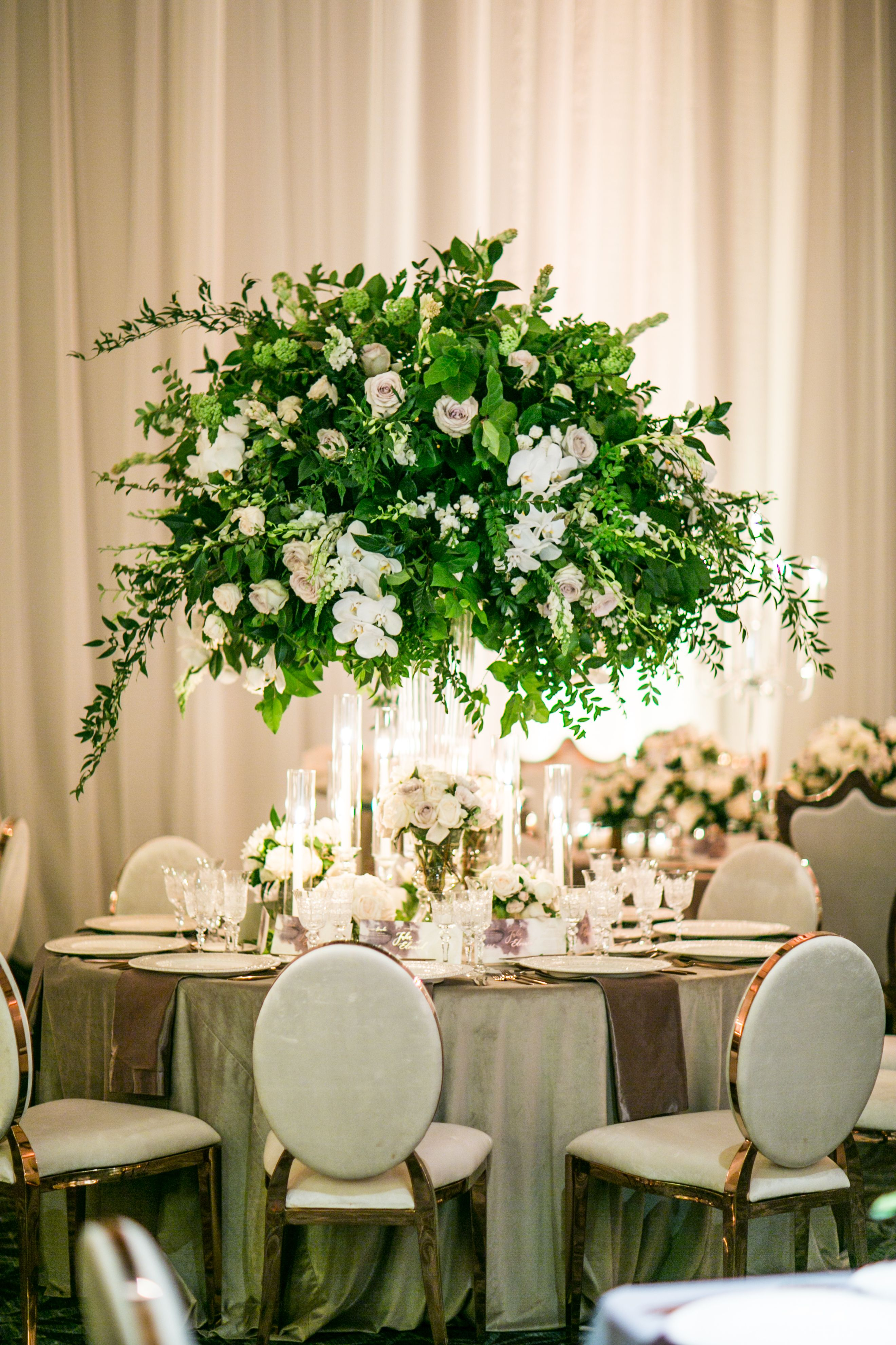 Tall Centerpieces Of Lush Greenery And White Florals Surrounded With Candles And Low Florals By Layers Greenery Centerpiece Large Centerpiece Tall Centerpieces