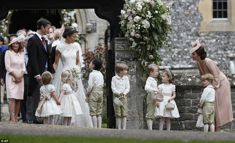 Duchess of Cambridge stands with her son Prince George as she looks across at Pippa Middle...