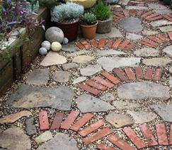 Coolest driveway, ever! Mosaic made of broken concrete, stone, bricks and gravel. (water easily passes through and back into the ground)
