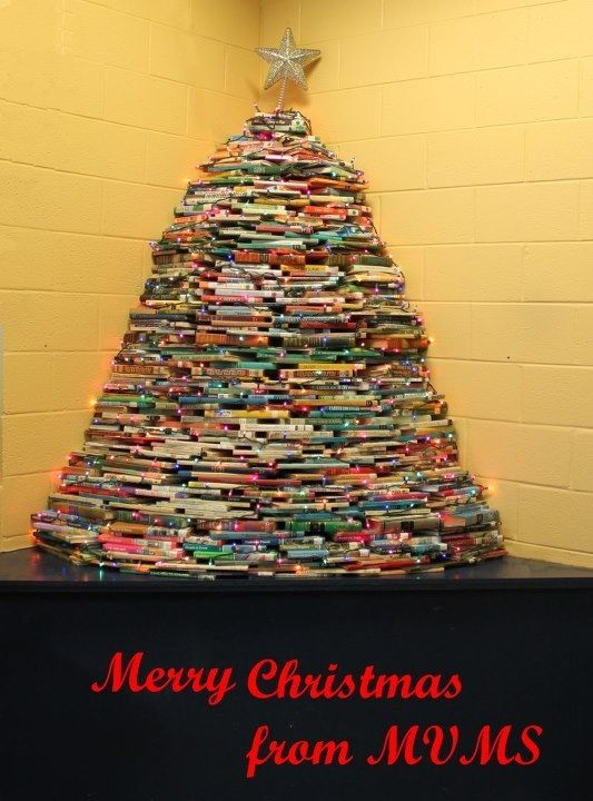 """Merry Christmas from Meridianville Middle! I made this tree from old """"weeded"""" books!!!    The key is to """"back fill"""" with large books.  I used A LOT of encyclopedias mixed with varying sizes of other books to fill the holes and support the tree.  The kids LOVE having it in our Library!!!"""