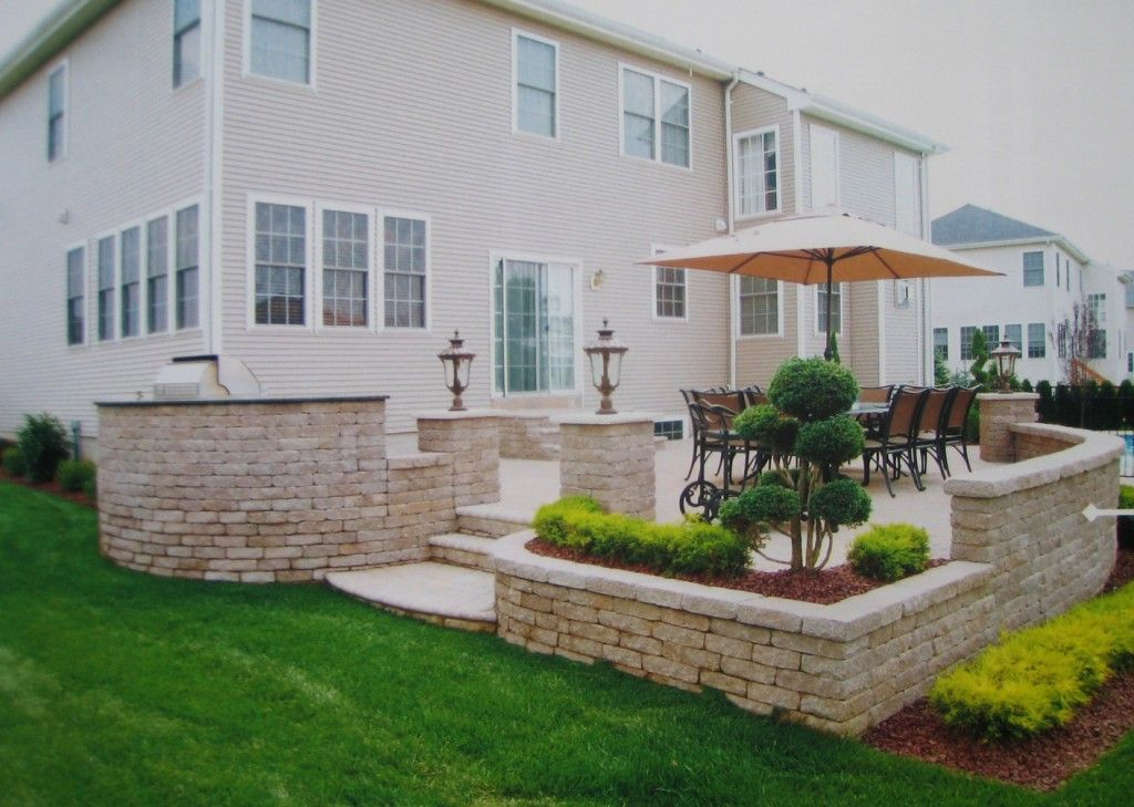 Raised patio stairs wall stone brick backyard retreats for Exterior garden design ideas