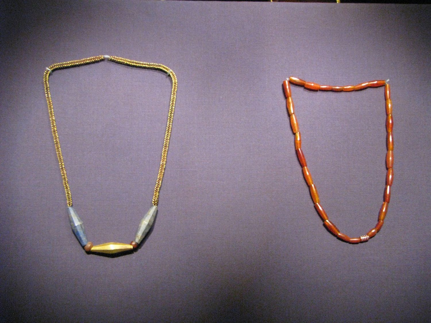 The headdress on the left is from the Ur royal cemetery. It is made of gold and lapis lazuli and would have been worn by a male. The necklace in the right is made of carnelian beads. It is also from Ur's royal cemetery and it has white etching, which was produced using a technique the Mesopotamians learned from the Indus Valley Civilization in South Asia.