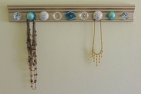 Gold wall hang up with Blue White and Gold Knobs and a Blue Stone