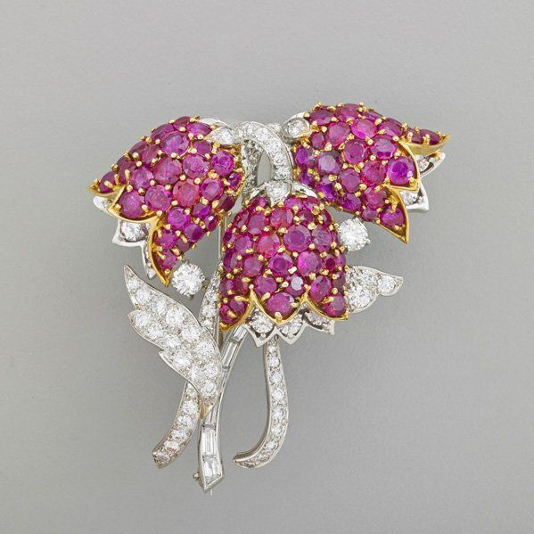 RUBY AND DIAMOND BOUQUET BROOCH. Platinum and 18k yg. designed in relief, three blossom comprises 71 round brilliant cut rubies, approx. 9 cts. TW, bead set in yellow gold, round brilliant and baguette cut diamonds and platinum foliage and stems, approx. 6 cts. TW, ca. 1960. Hinged double pin back. Retailed by Verdura.