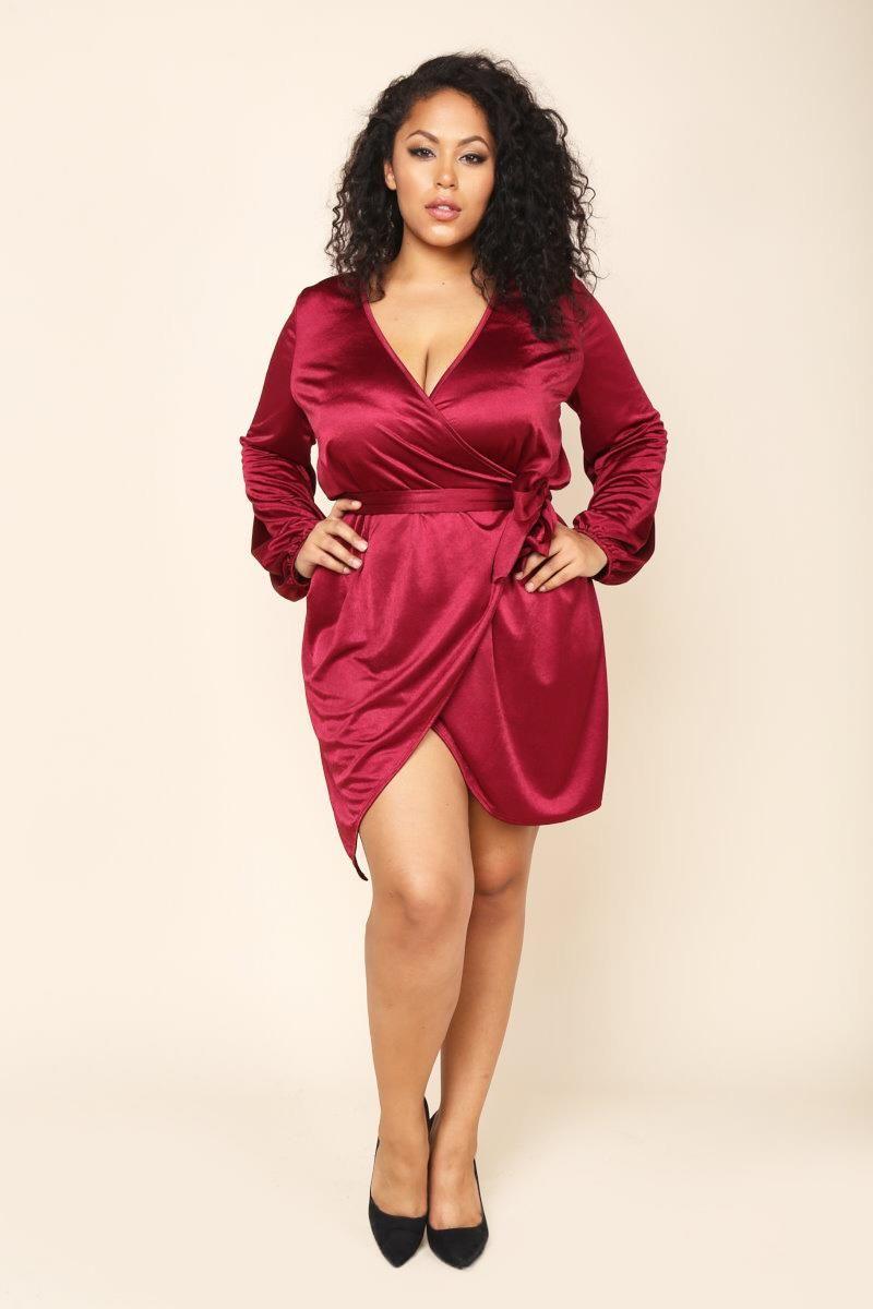 A plus size mini wrap dress with a surplice V-neckline and long ...