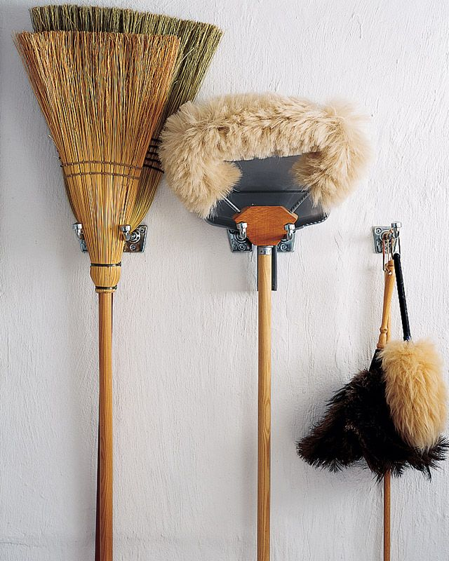Wall hooks keep an assortment of brooms and mops off the floor.
