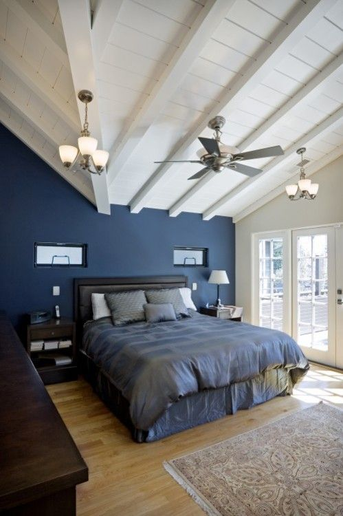 A Dark Blue Bedroom Is Lightened With A White Vaulted Wood Ceiling