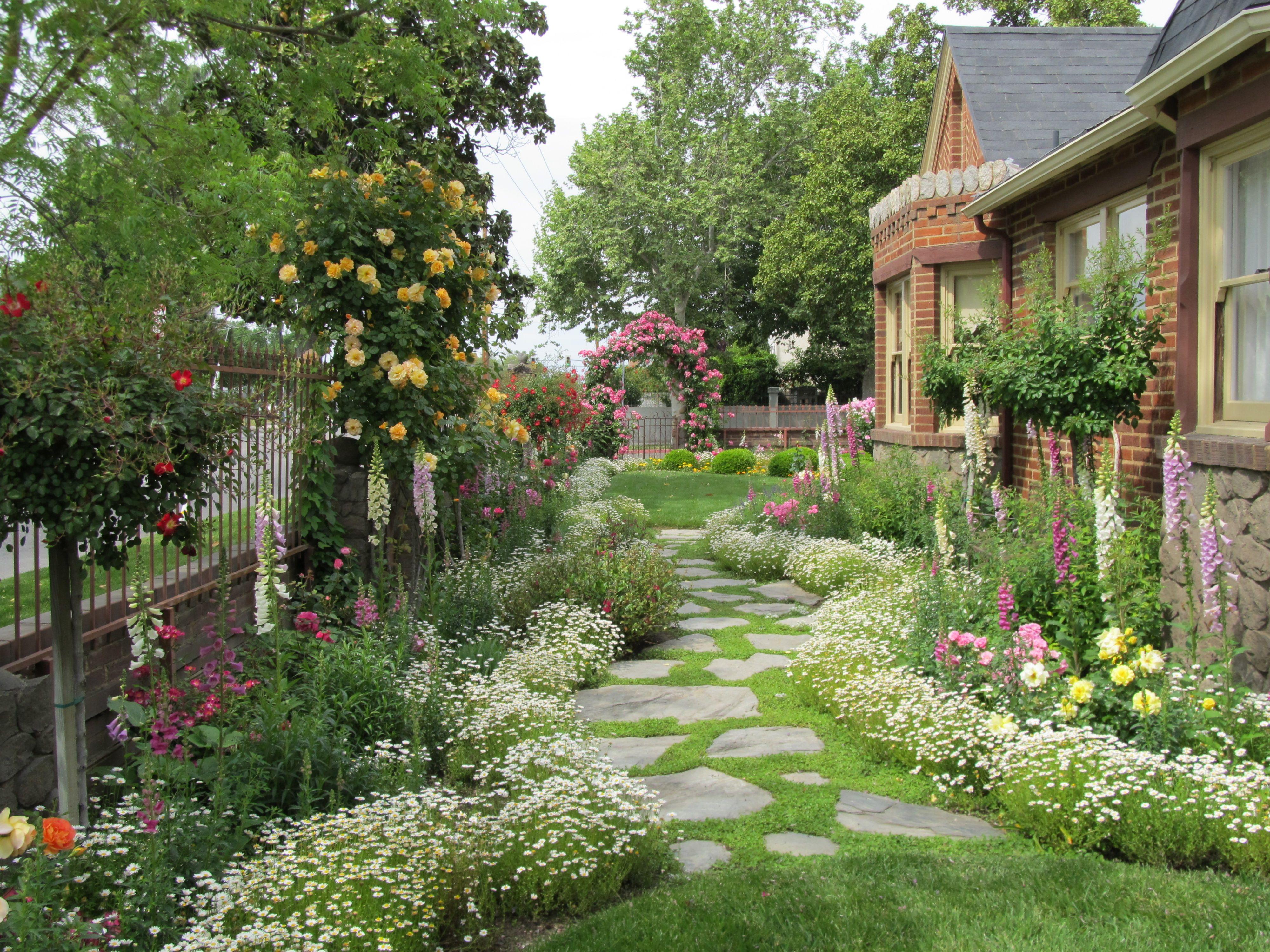 Flagstone path going towards rose arbor country cottage for Modelos de jardines para casas