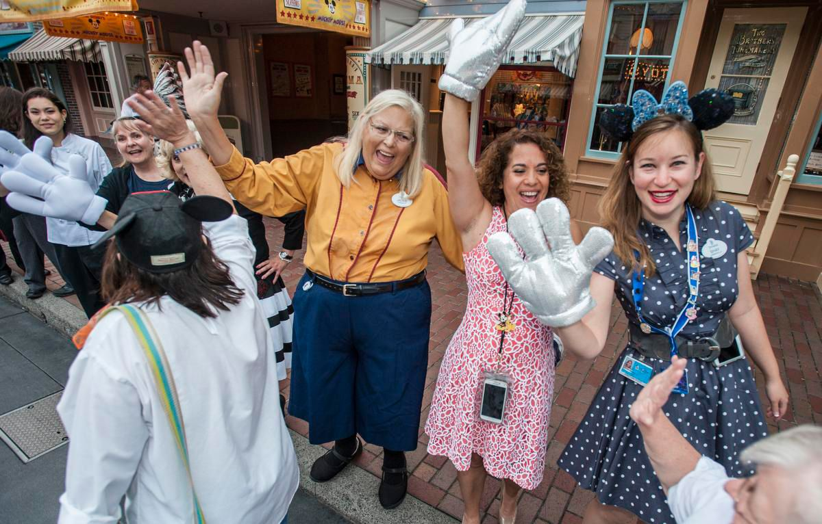 Disneyland cast members greet guests along Main Street USA during Disneyland's 60th birthday celebration Friday morning. http://www.ocregister.com/articles/disney-672399-disneyland-park.html
