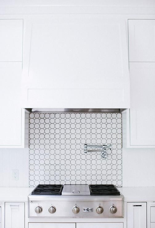 A White Wood Hood Is Mounted To Octagon Backsplash Tiles Between Stacked Shaker Cabinets And