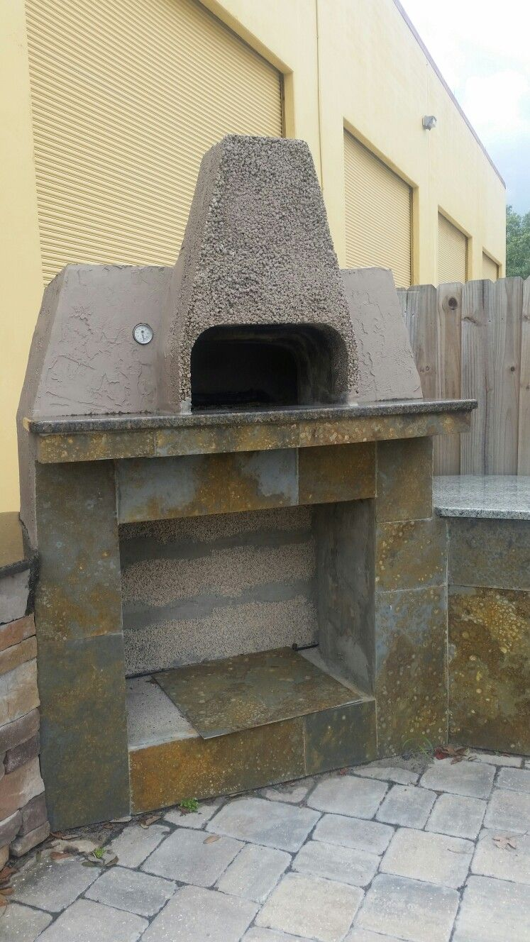Outdoor kitchen with wood fire pizza oven and stone facing