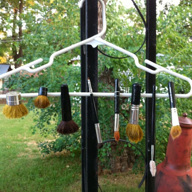 DIY makeup brush drying rack!  Use tiny rubber bands to attach brushes to a hanger. Place brushes upside down so they will dry without losing their shape.