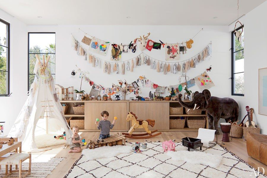 Bohemian modern kids playroom - Moroccan rug, white walls, black steel windows, mid century storage - This room can mature with your children and their hobbies.