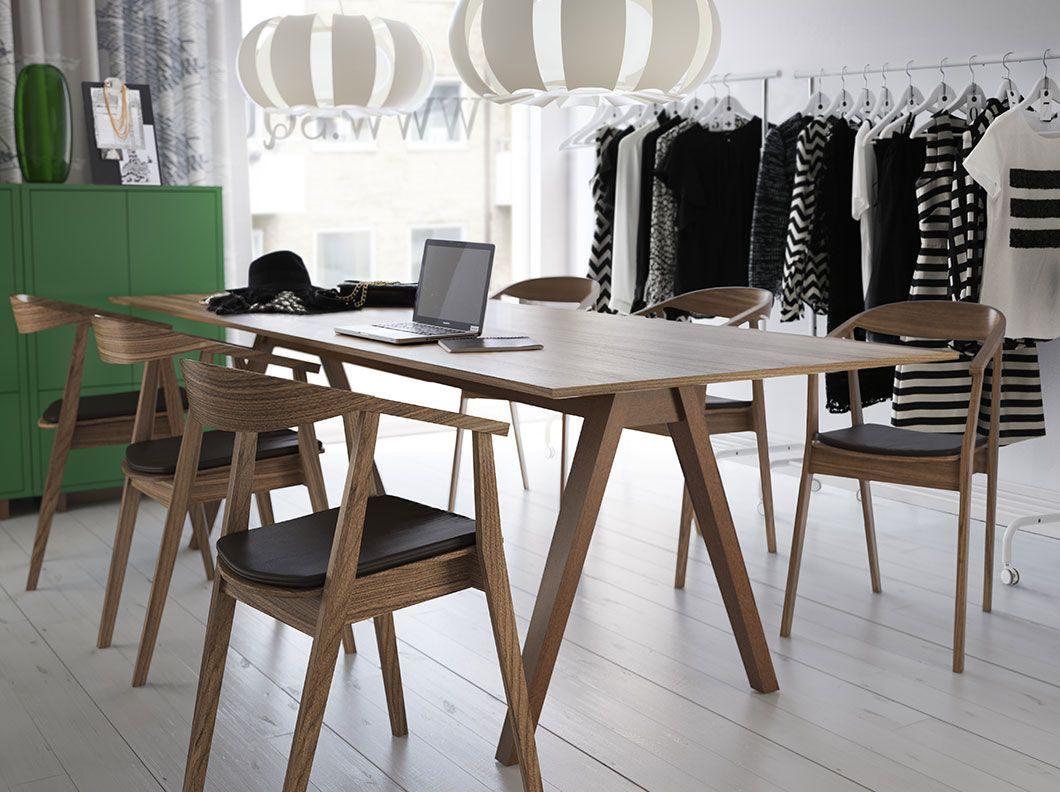 Konferensrum med långt bord i valnötsfaner och stolar med lädersits