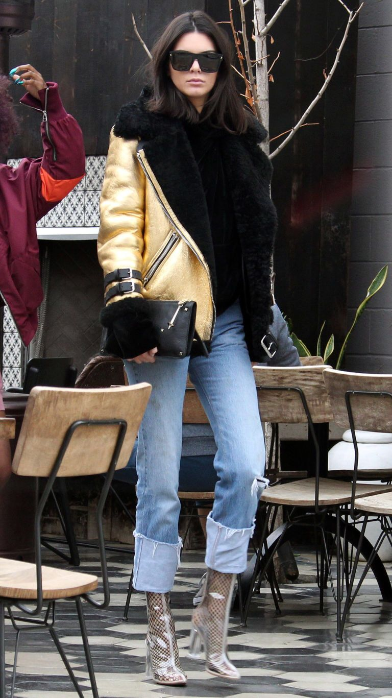 January 2, 2016  In a metallic leather and black shearling jacket, hoodie, black leather clutch, cuffed distressed jeans, Givenchy sunglasses, fishnet tights and transparent boots while out in West Hollywood.