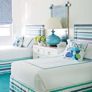 Twin beds decked out in turquoise and nearly indigo blue pop against crisp white walls in designer Meg Braff's West Palm Beach bedroom. White bedding with a turquoise Greek key pattern is topped with fun floral throw pillows that tie the color scheme toge