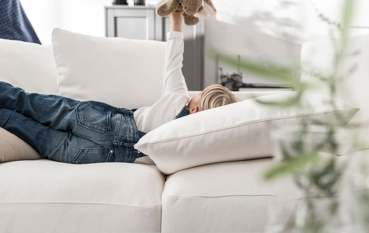 A Child Lying On A White Sofa Playing With A Soft Toy Comfort Words Ikea Couch Ikea Sofa Reviews