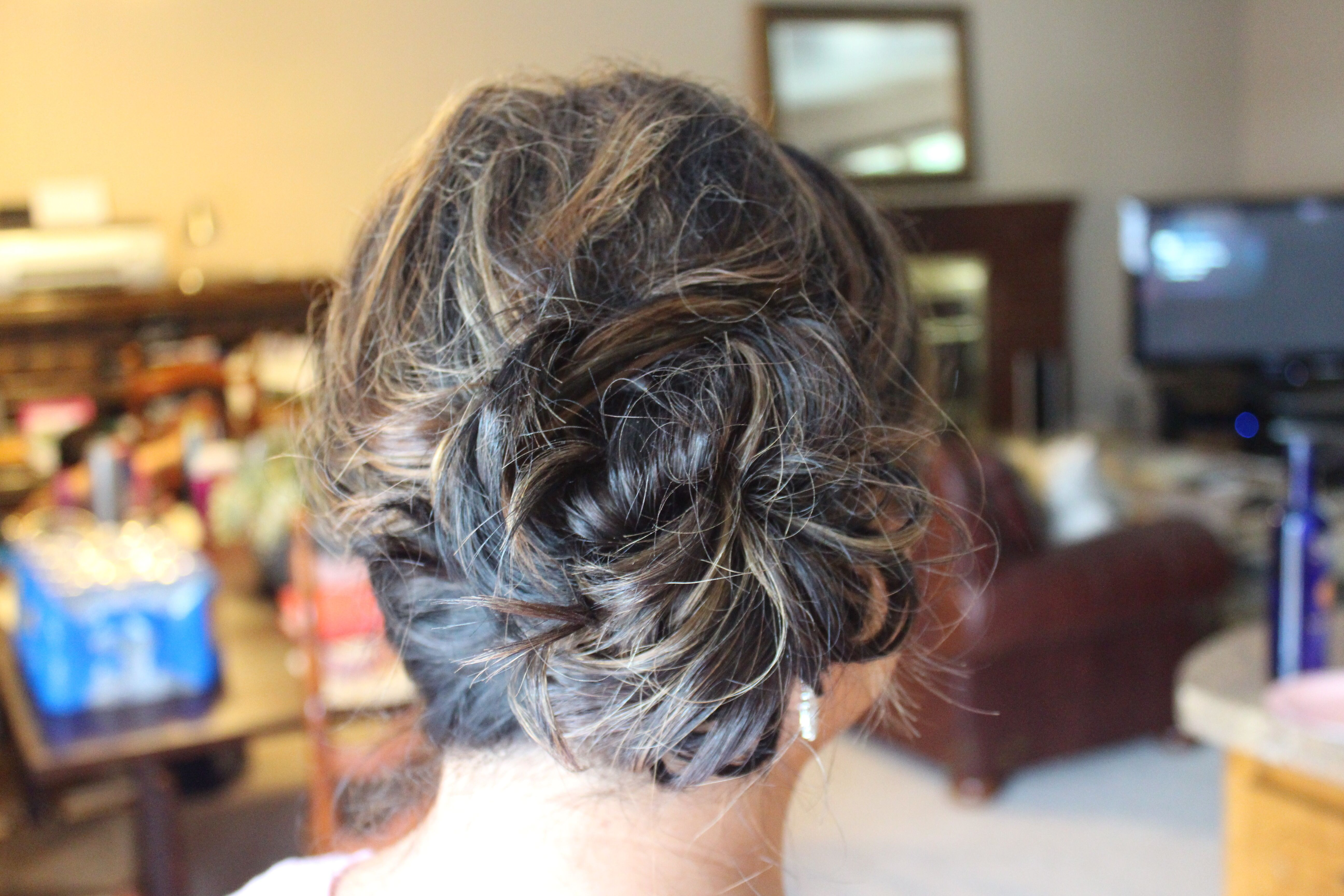 A beautiful side messy bun on shoulder length hair completes this