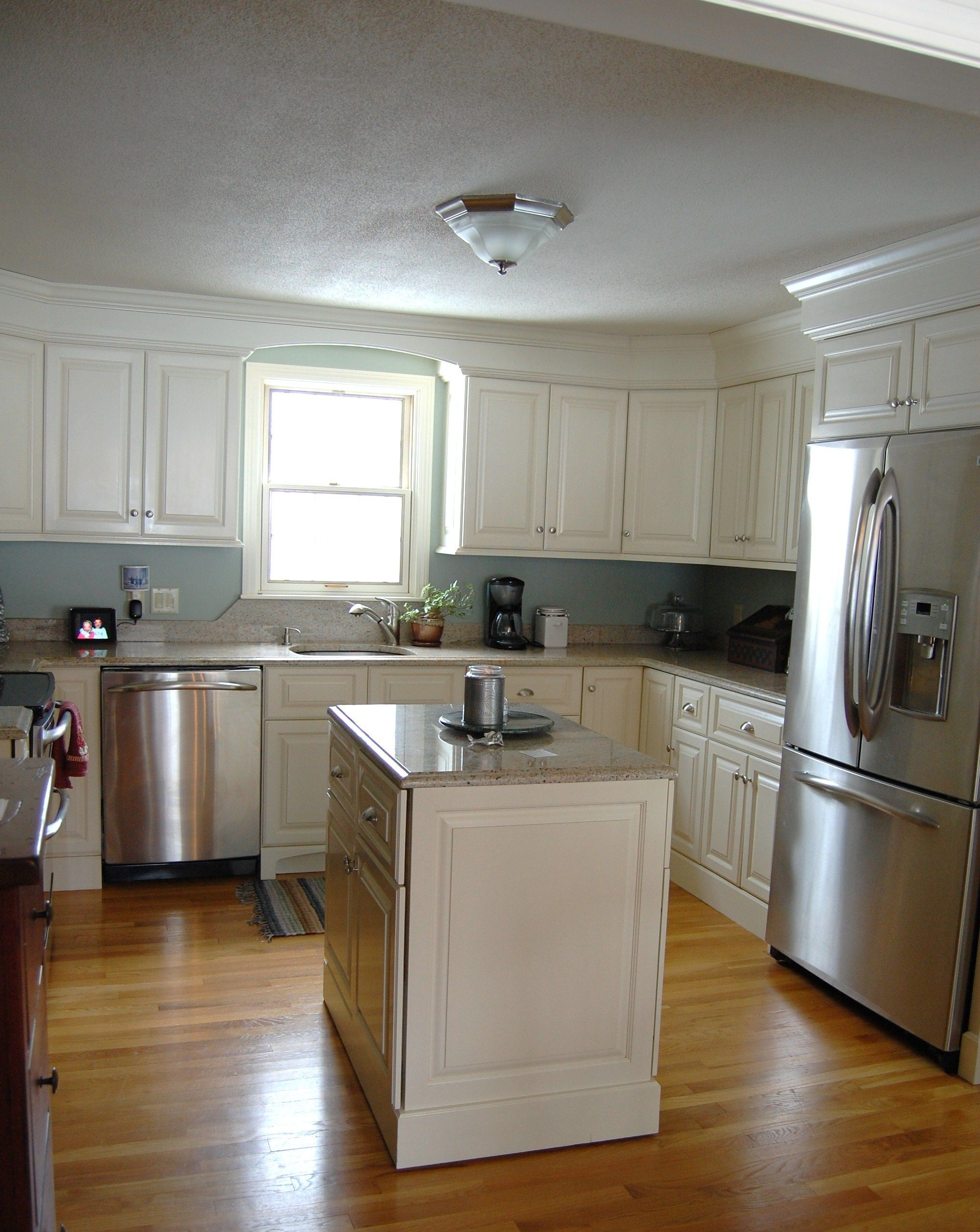 This cozy island shaped transitional kitchen layout for Light colored kitchen cabinets
