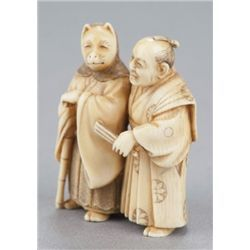 An ivory netsuke of the fox priest and village hea