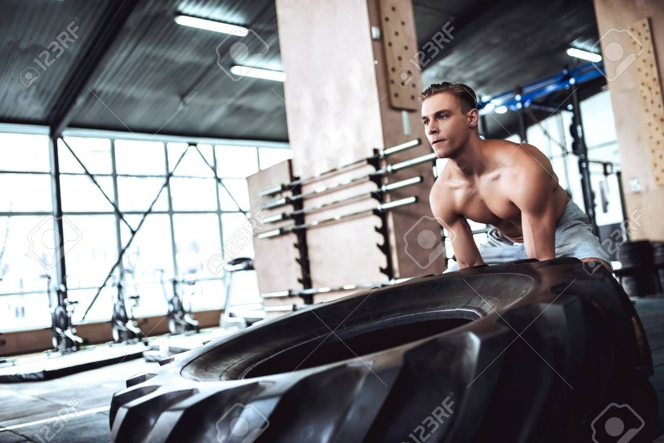 Strong muscular man is working out in gym. Cross fit training. Pushing tire. Stock Photo ,