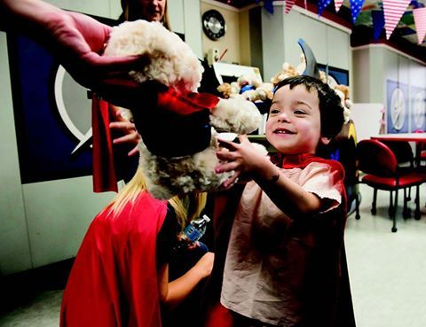 Benjamin Ramroop, 3, grabs a stuffed bear as employees from Bristol-Myers Squibb donned superhero capes to visit our patients and deliver 250 stuffed bears.