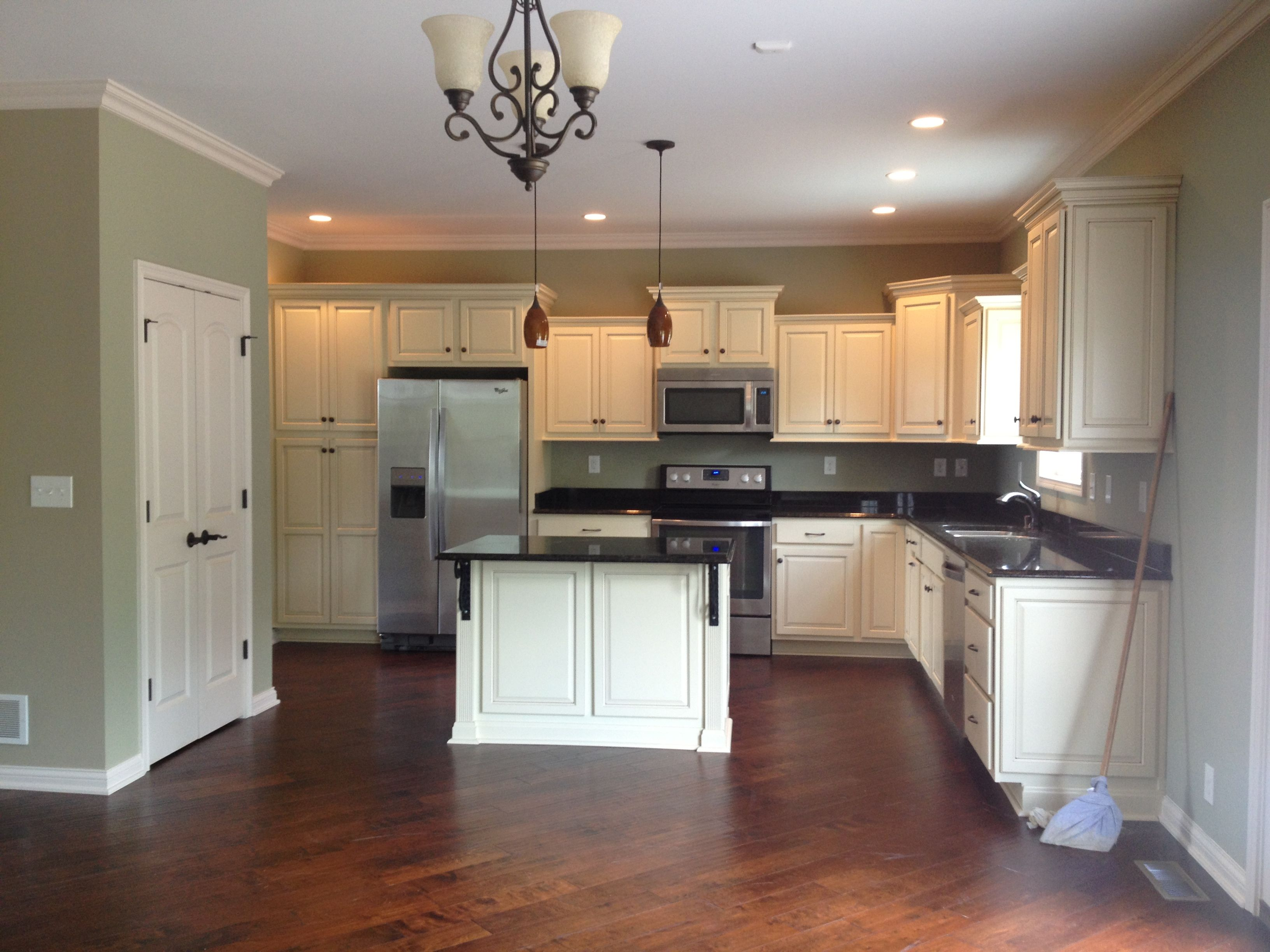 White cabinets w/black tops and dark wood floor. Green walls ...