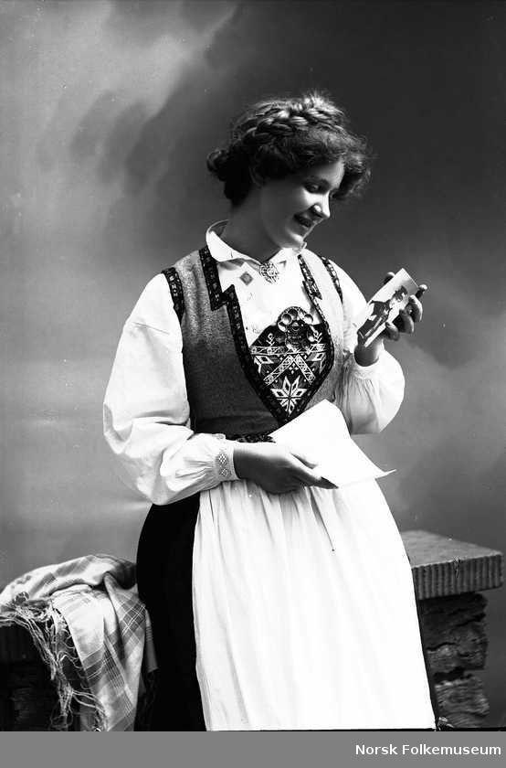 Digitalt Museum - Studioportrett av jente i drakt og oppsatt hår. Hun holder et bilde av en mann i den venstre hånden som hun ser ned på, og et brev i den høyre. Hun lener seg mot et gjerde. Til høyre for henne ligger et skaut. Fotograf: Solveig Lund