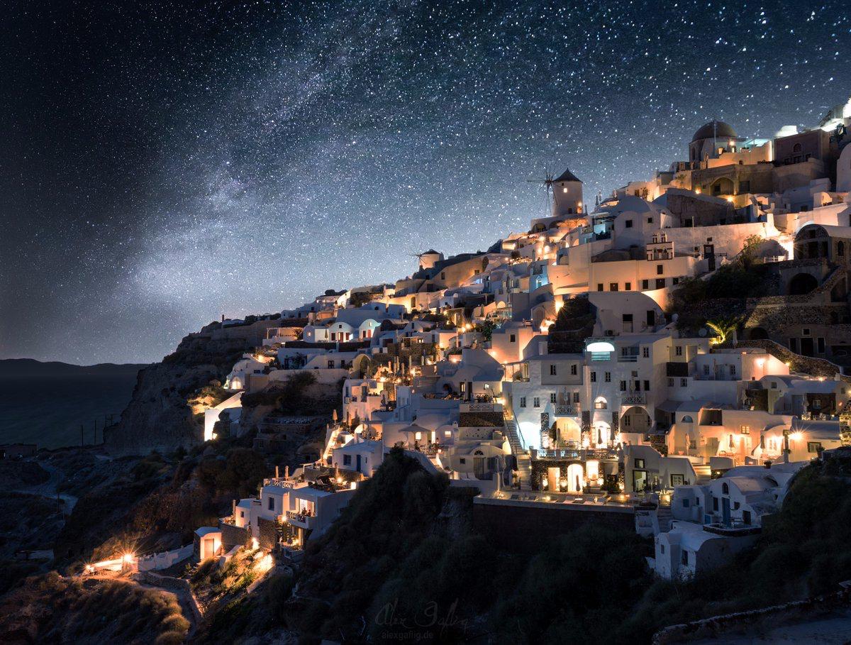 ギリシャ・キクラデス諸島の海沿いの斜面に広がる集落の夜景。 bit.ly/2aEb9Uw 地中海地域の白壁の建物は青空によく映えるが、星空を背景にした夜景も美しい。ドイツの写真家 @alexgaflig 氏の作品。