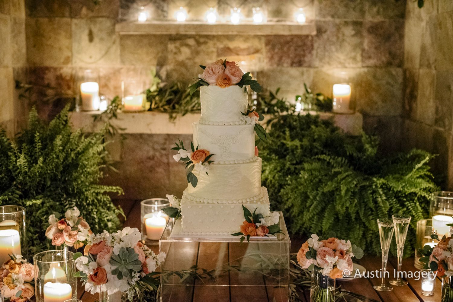 Clusters of pillar candles and green Boston ferns in the base of the grotto and gold mercury glass votives on the ledges