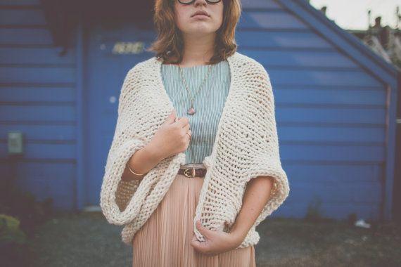 El suéter de punto grueso sobredimensionado encogiéndose de hombros