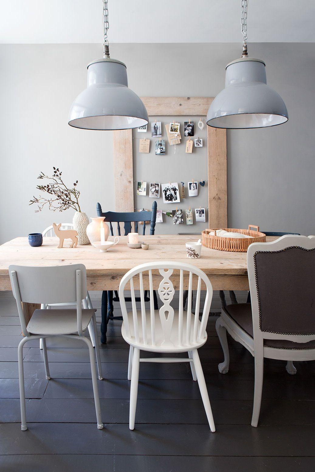 Houten tafel met stoelen in verschillende vormen en kleuren voor een