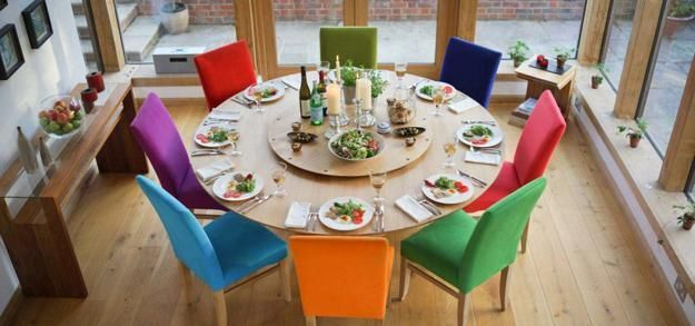 Round Dining Table Made Of Wood With Colorful Upholstered Chairs