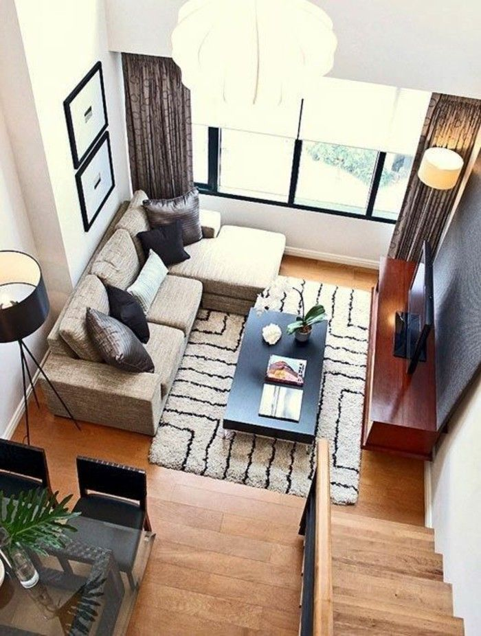 high angle image showing a bright room with a beige corner sofa a patterned beige and brown rug and wooden laminate floor simple living room designs