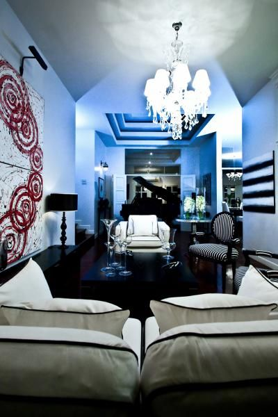 monochromatic living room with blue light effect white and red abstract art white sofa with black piping and glossy black table - Light Blue And Black Living Room
