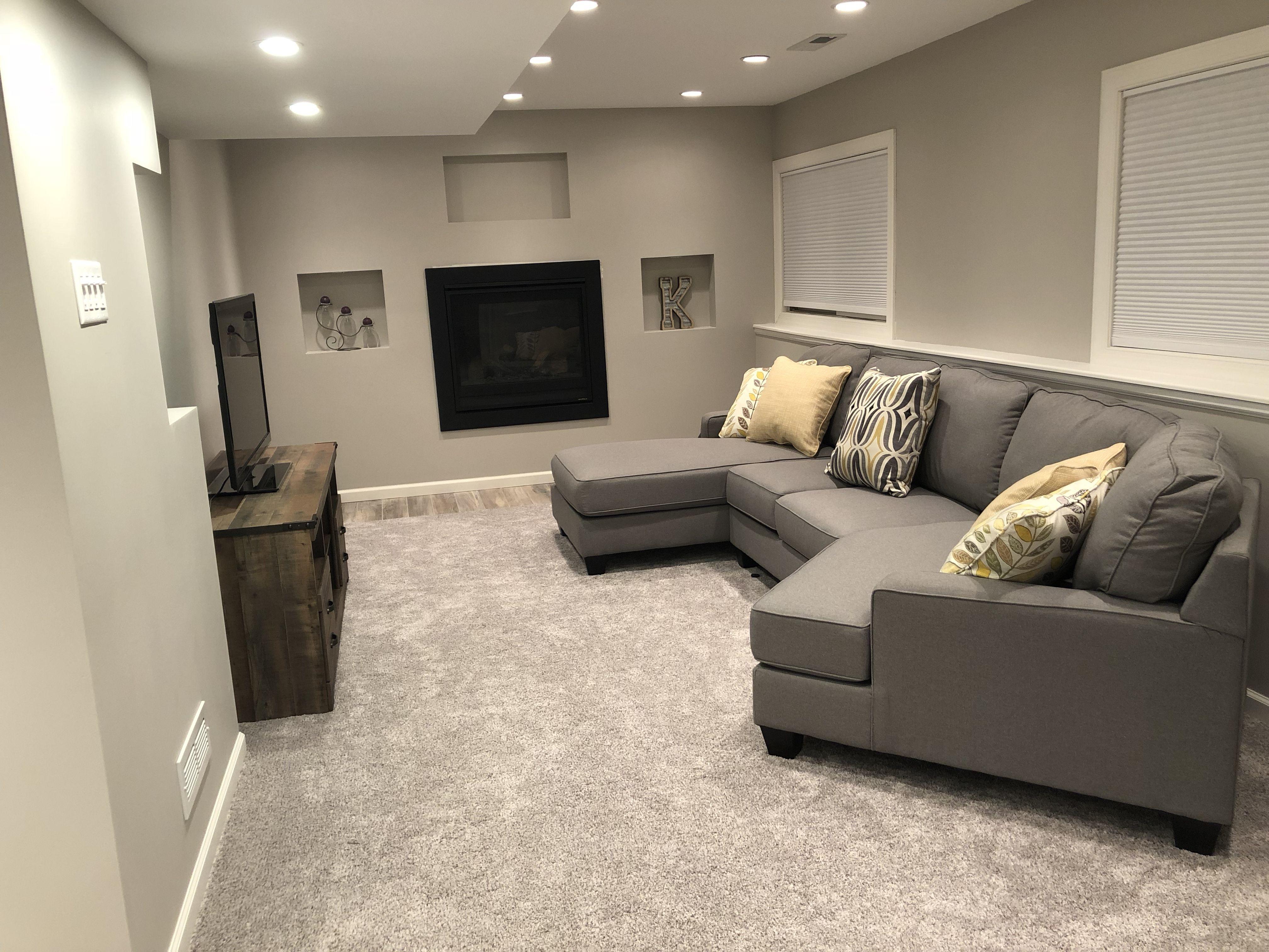 Long narrow basement family room. Minimalist. Gray sectional