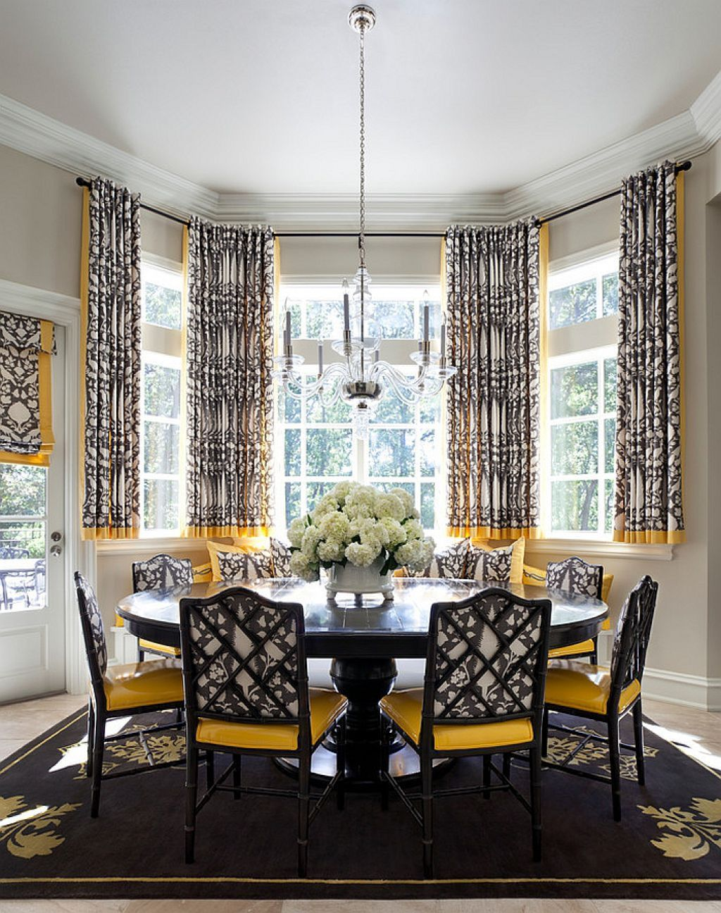 Dining Room Bay Window Covered With Short Curtains And Furnished Round Table Armless Chairs