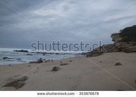 Dark rocks in a blue ocean under cloudy sky in a bad weather. Long exposure photography - stock photo