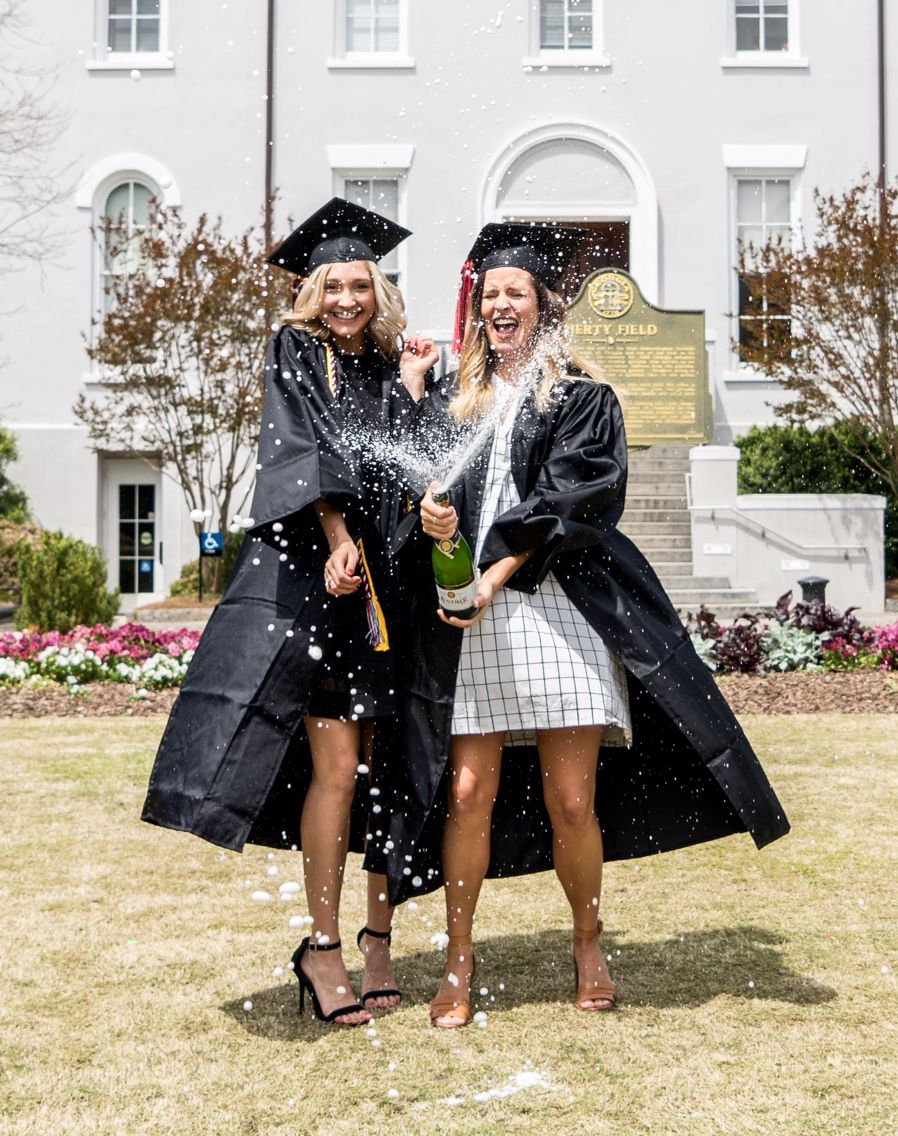 College graduation photos with my best friend! Popping a bottle of champagne on campus #graduation #uga #champagne #graduationphotos