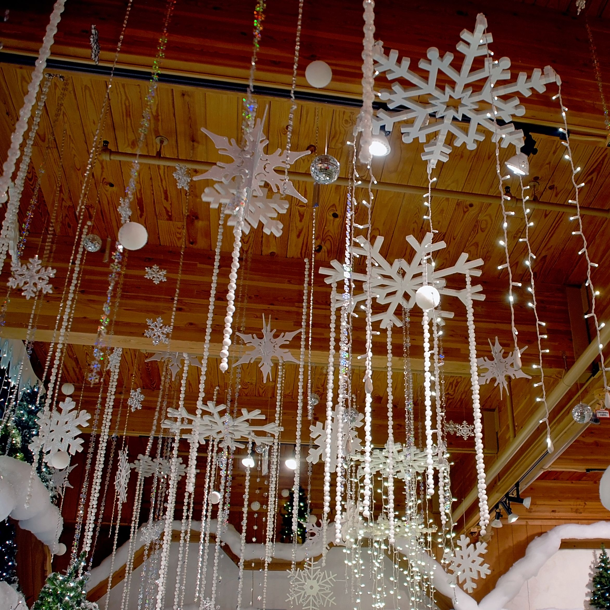 Snowflakes And Twinkling Lights Hang From The Ceiling Above Bronner S Christmas Ceiling Decorations Winter Wonderland Decorations Office Christmas Decorations
